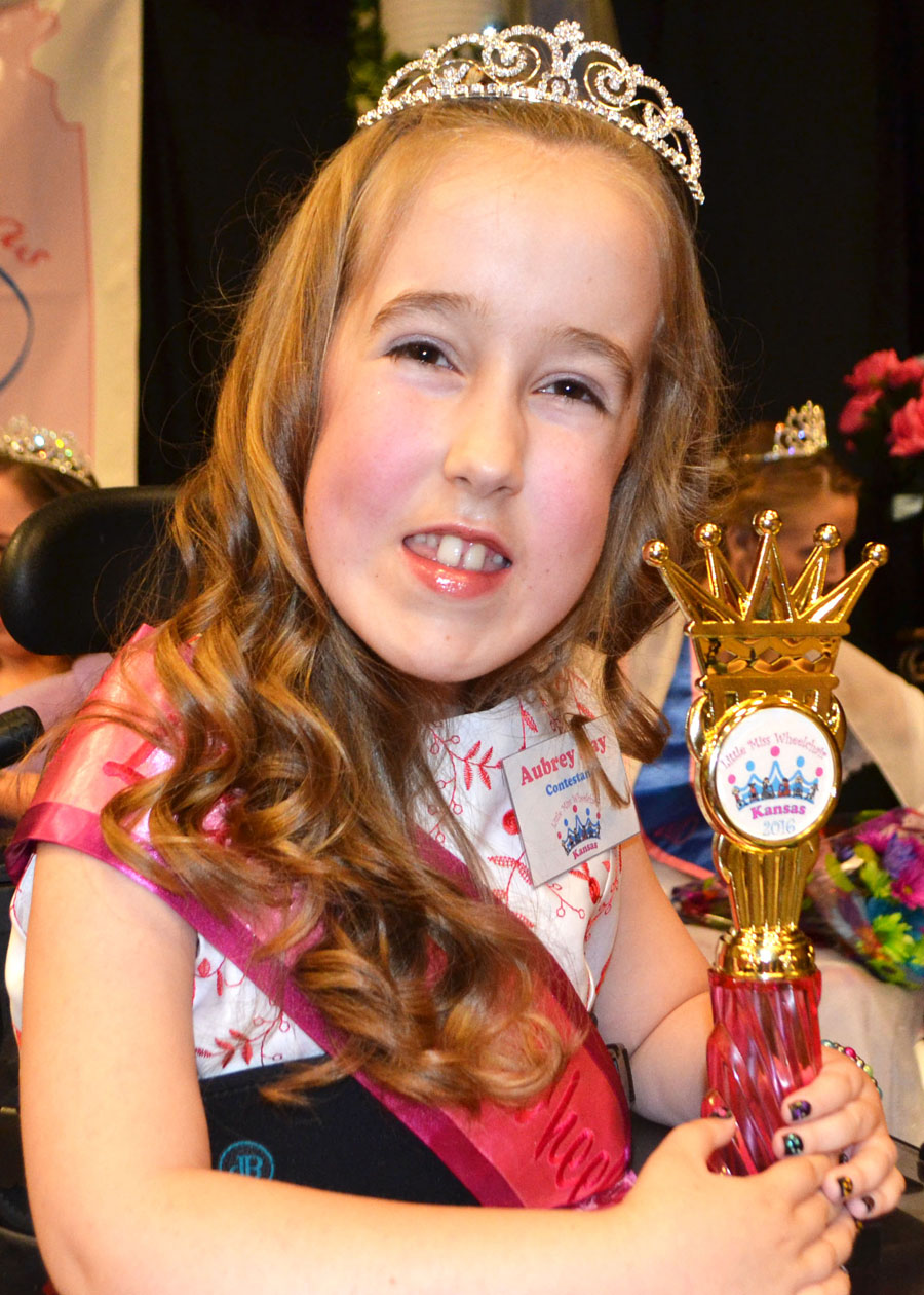 Aubrey wearing her crown and sash and holding up her trophy