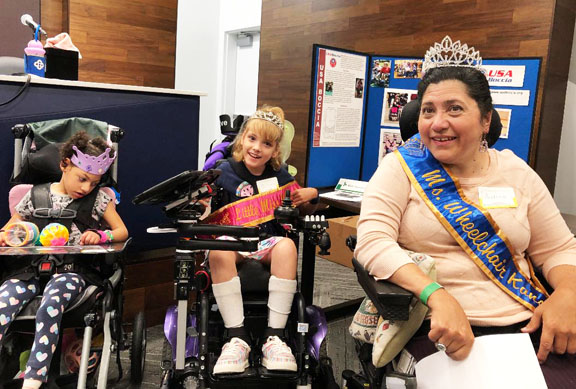 Little Miss titleholder at an event with Ms. Wheelchair Kansas and another little girl